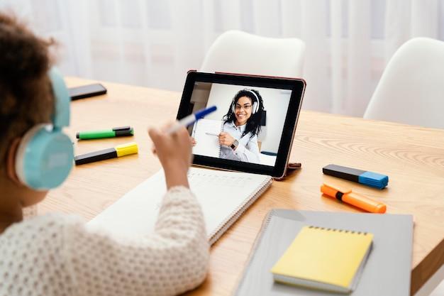 태블릿 및 헤드폰 온라인 학교 동안 어린 소녀