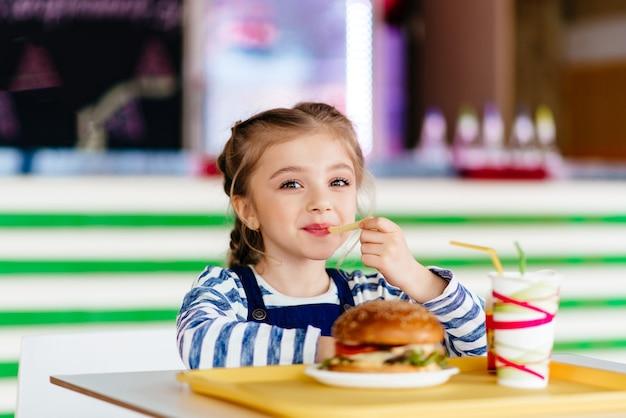 Маленькая девочка ест гамбургер в летнем кафе