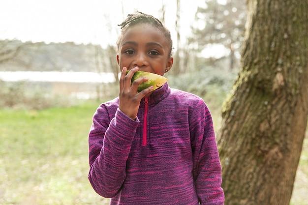Маленькая девочка ест арбуз