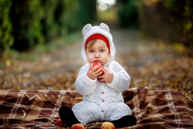 秋の公園でリンゴを食べて毛布の上に座っている少女。