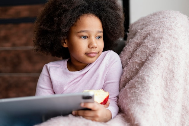 Little girl eating apple and using tablet