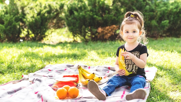 Little girl eating banana at picnic in the park