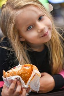 ファーストフードカフェでハンバーガーを食べる少女。