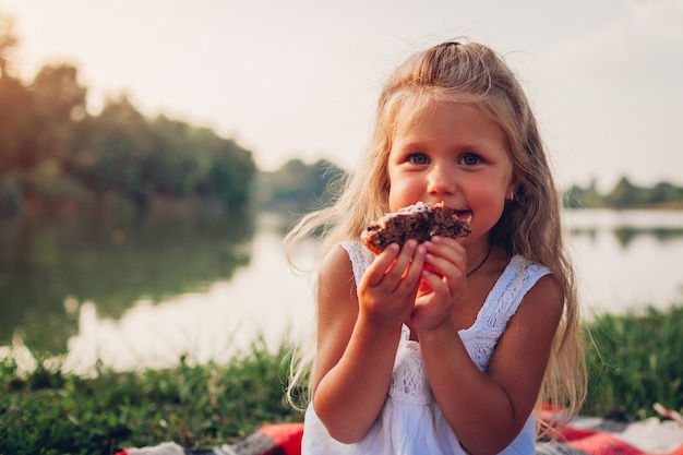 Little girl eating cake on family picnic by summer river, child holding pie