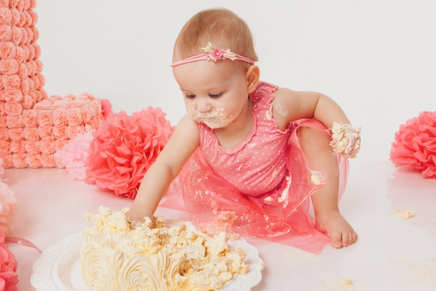 Little girl eating cake with her hands on white . the child is covered in food. ruined the sweetness.  birthday, holidays, cooking