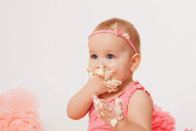 Little girl eating cake with her hands on white