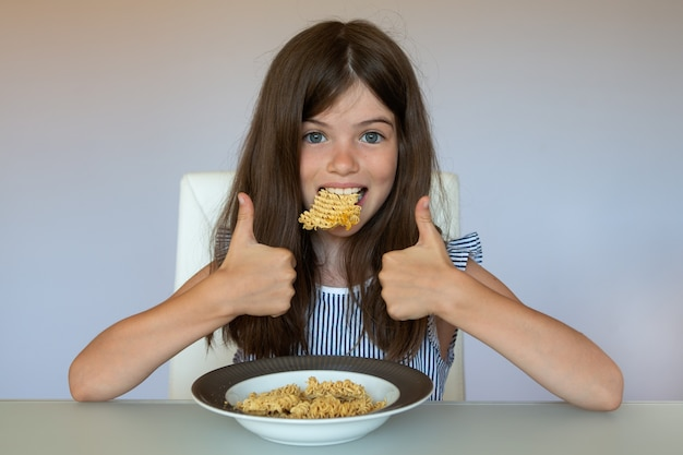 Little girl eating chinese instant noodles, unhealthy eating concept, food addiction