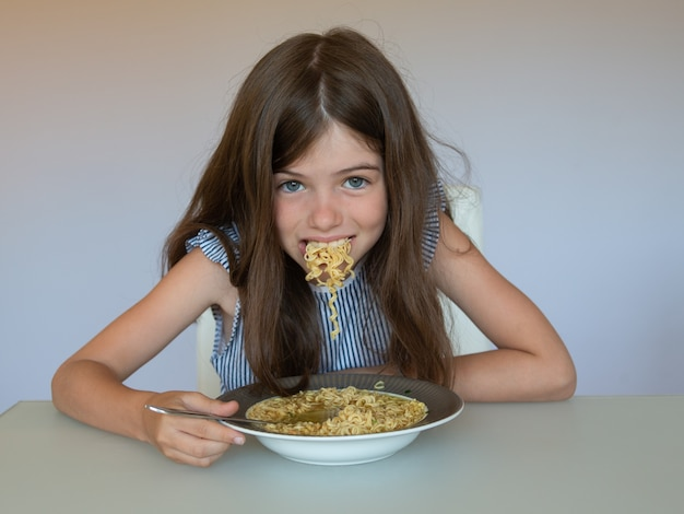 Маленькая девочка ест китайскую лапшу быстрого приготовления