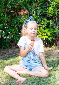 屋外でチョコレートアイスクリームを食べる少女