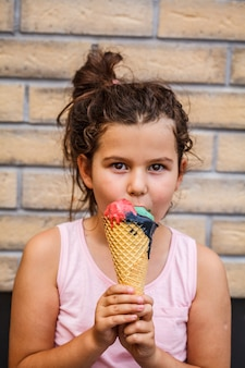 Little girl eating colored ice cream with charcoal and spirulina on the street.