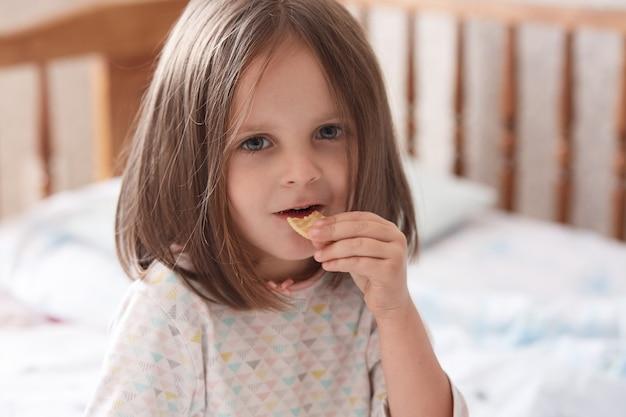 ベッドに座ってクラッカースナックを食べる少女