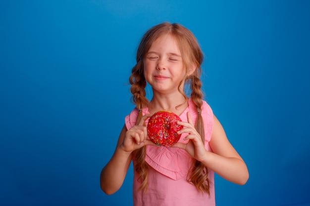 A little girl eating a donut