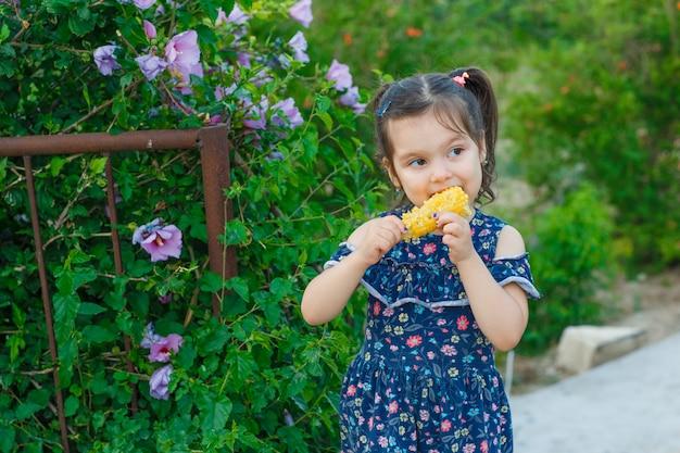 庭、正面の春のドレスに立ちながら新鮮なトウモロコシを食べる少女。