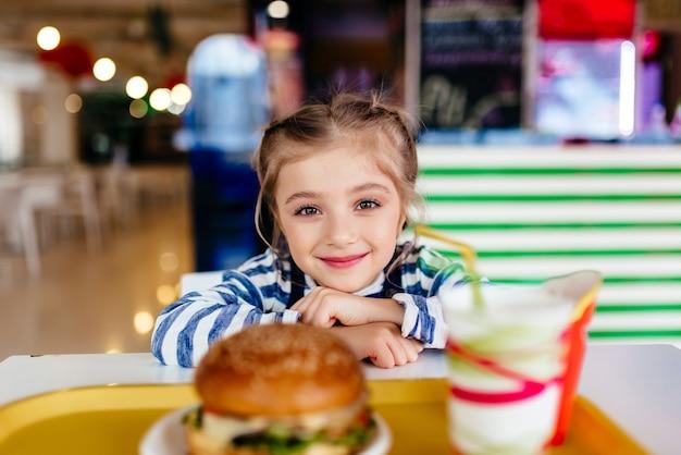 Маленькая девочка ест гамбургер и картофель фри в ресторане быстрого питания