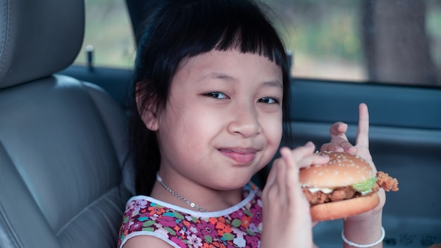 笑顔で幸せな車でハンバーガーを食べる少女