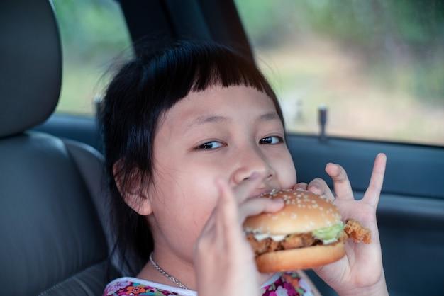 미소와 행복 차에 햄버거를 먹는 어린 소녀