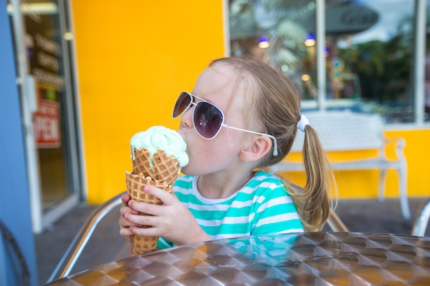 Little girl eating ice cream in a cafe outdoor