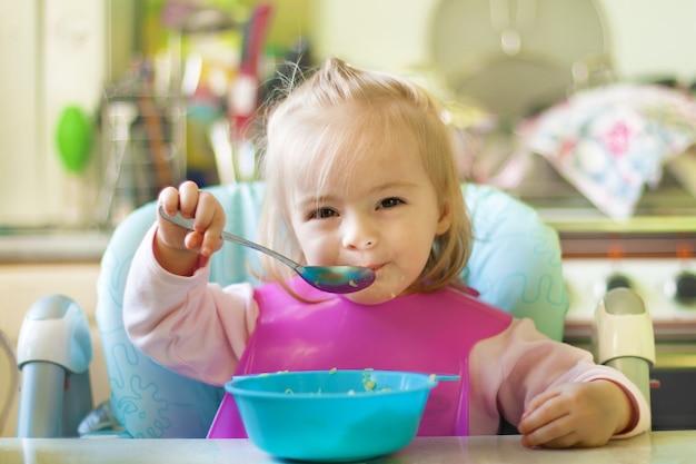 Маленькая девочка ест на кухне