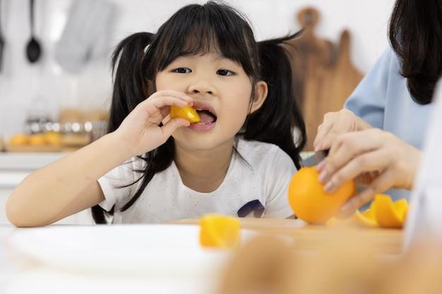 Little girl eating oranges