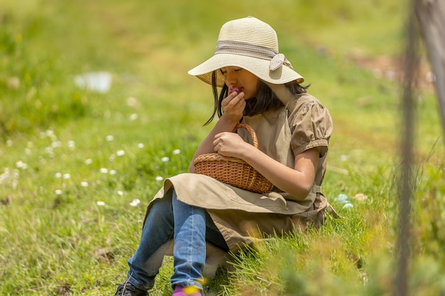 Little girl eating peaches in the field