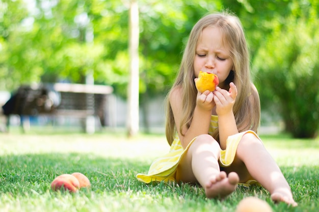 Little girl eating peaches in the park