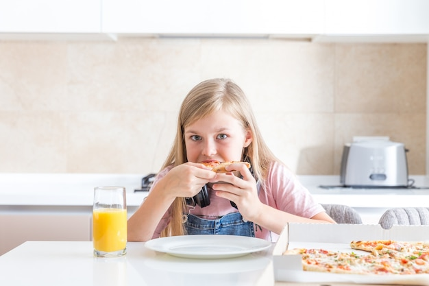 Little girl eating pizza sitting at the table