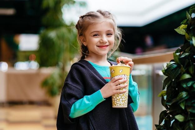 Маленькая девочка ест попкорн в помещении