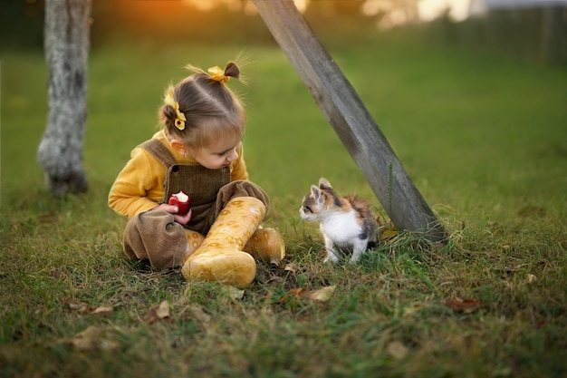 Little girl eating red apple.  girl sitting with a kitten