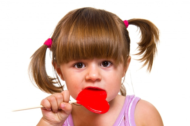 Little girl eating red heart lollipop