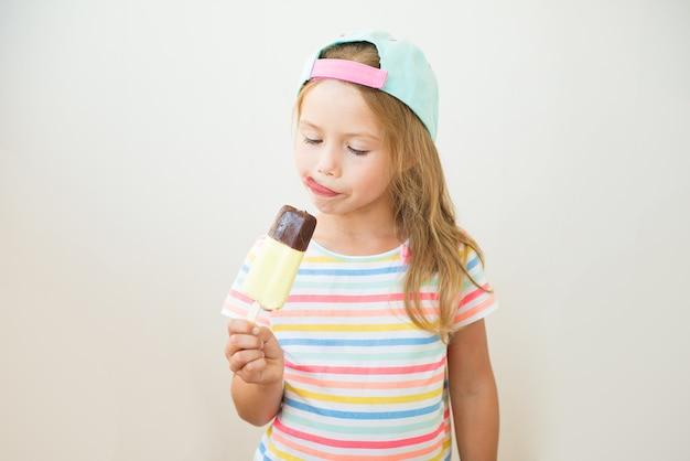 棒で甘いアイスクリームを食べる少女