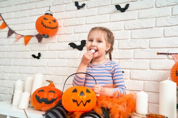 Little girl eating sweets from a pumpkin bucket