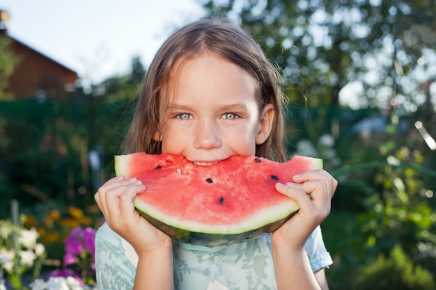 Little girl eating watermelon in nature.