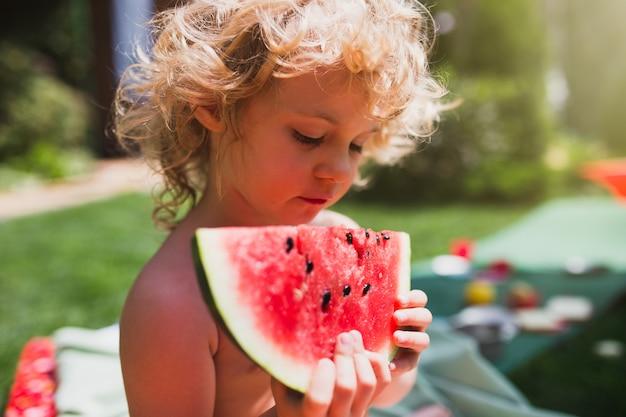 여름에 잔디에 수박을 먹는 어린 소녀