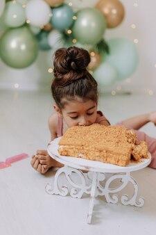 小さな女の子は、誕生日の概念の風船で飾られた部屋で正方形の層のケーキを食べる