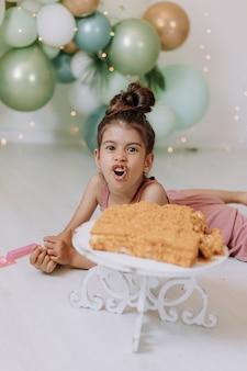 小さな女の子は、休日の概念の風船で飾られた部屋で正方形の層のケーキを食べる