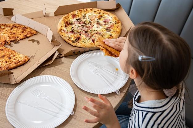 어린 소녀는 점심에 식욕을 돋우는 치즈 피자를 먹는다. 맛있는 치즈 피자.
