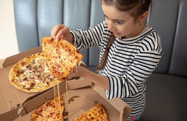 어린 소녀는 점심에 식욕을 돋우는 치즈 피자를 먹는다.