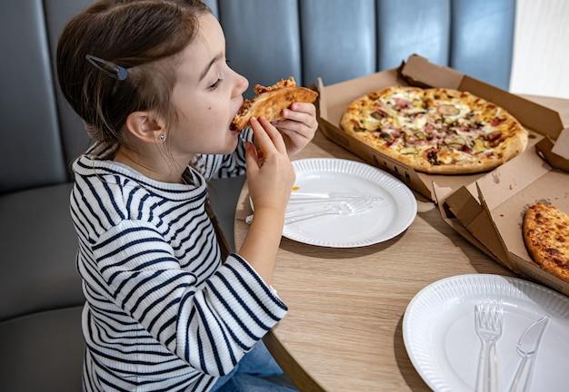 La bambina mangia appetitosa pizza al formaggio per il pranzo.