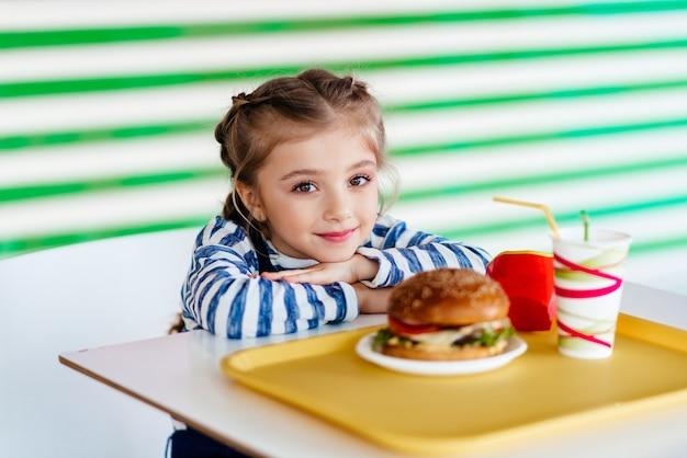 Маленькая девочка ест гамбургер в закусочной