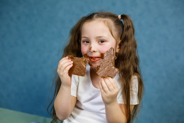Маленькая девочка ест шоколад, пачкает свою белую футболку, лицо и протягивает ему руку