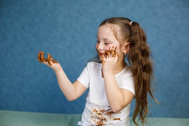 小さな女の子はチョコレートを食べ、彼女の白いtシャツを汚し、顔をして彼に手渡します