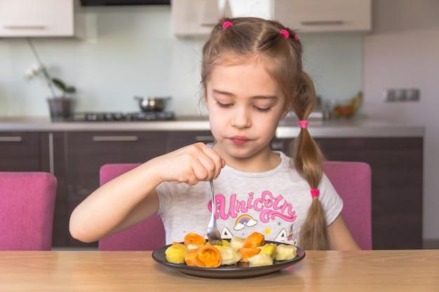 Маленькая девочка ест красочные пельмени.