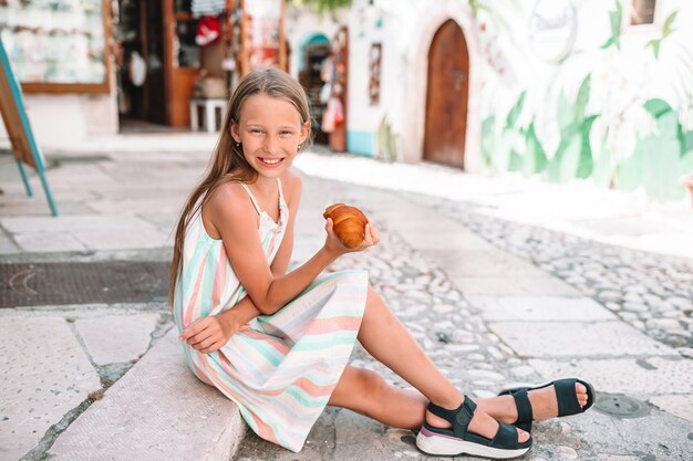 Little girl eats croissant on old streets in european village