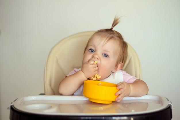 小さな女の子は台所のテーブルでおいしいパスタを食べます