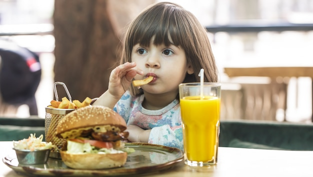 Little girl eats in a fast food cafe