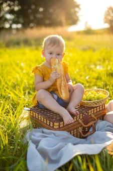 어린 소녀는 자연의 일몰 조명에서 피크닉에서 신선한 바게트와 과일을 먹습니다