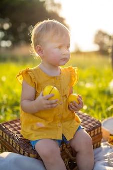 어린 소녀는 자연의 일몰 조명에서 피크닉에서 신선한 과일을 먹습니다