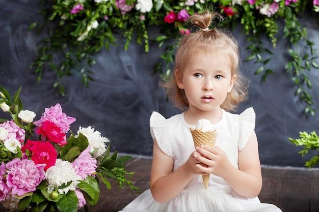 Маленькая девочка ест мороженое. цветочный декор в интерьере. портрет прекрасной девушки