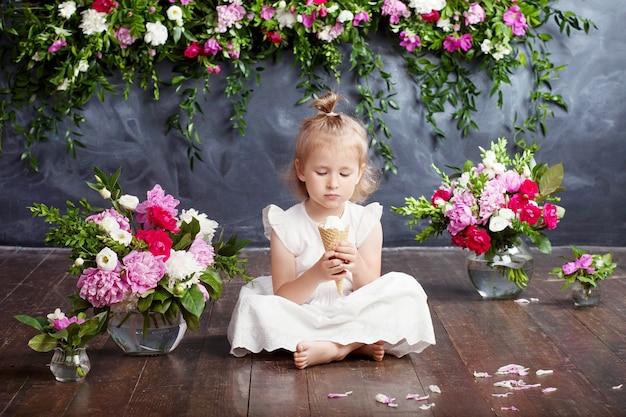 Маленькая девочка ест мороженое и смеется. цветочный декор в интерьере. портрет эмоциональной милой девушки