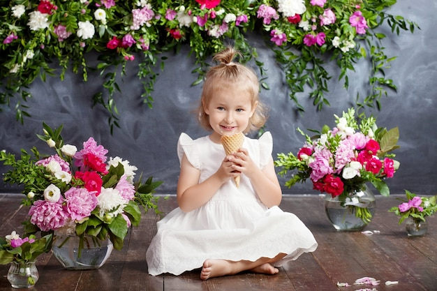 Little girl eats ice cream and smiles. a flower decor in an interior. portrait of the emotional lovely girl